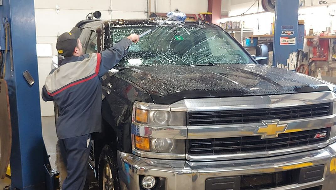 Technician cleaning the exterior of a Chevy truck
